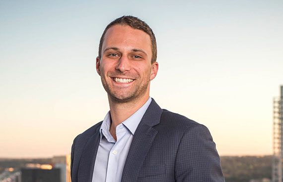 a business portrait/headshot of a smiling man standing on a rooftop downtown