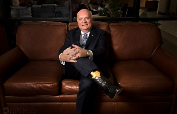 a business portrait of Moody Bank CEO Victor Pierson sitting on his office couch