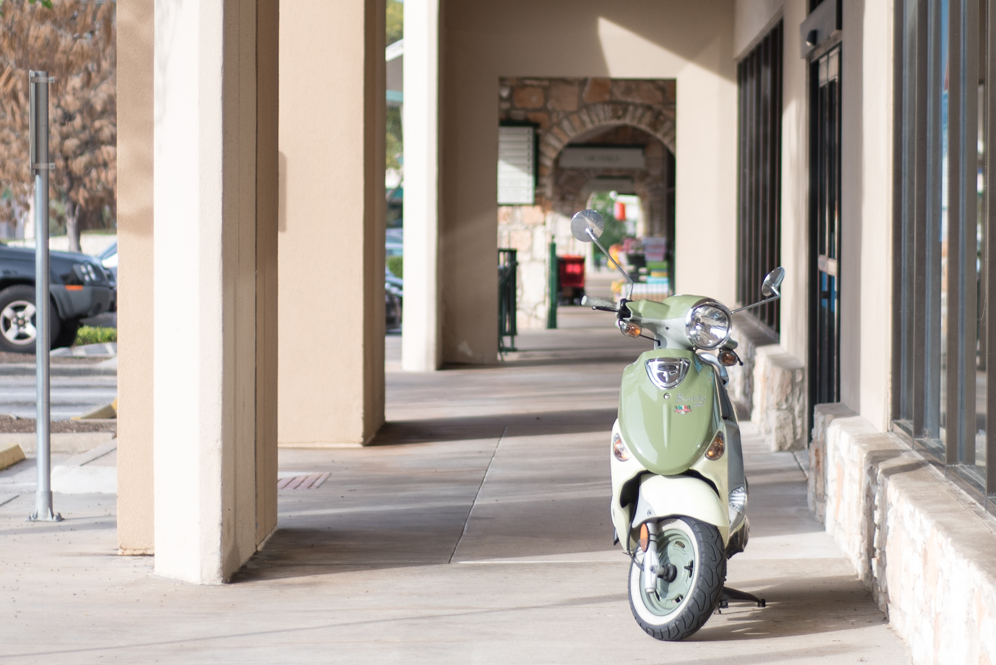a photo of a green scooter in a walkway at West Woods Shopping Center in Austin TX