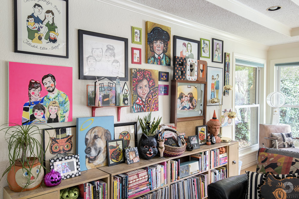 a living room wall full of picture frames and a bookshelf with decorations on it