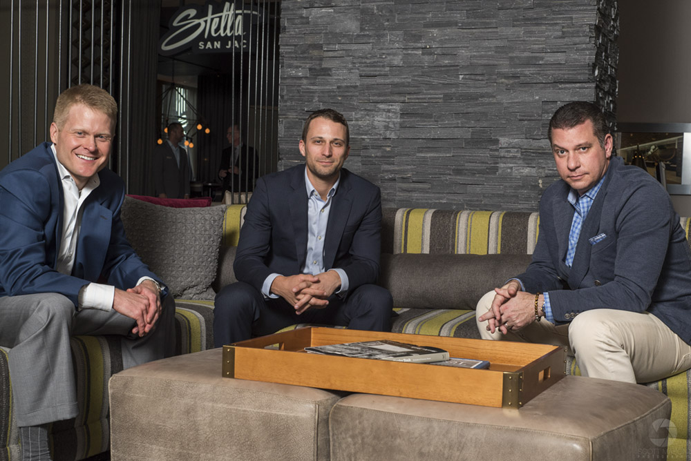 a photo of three men in business suits sitting at a table having a meeting, looking into the camera