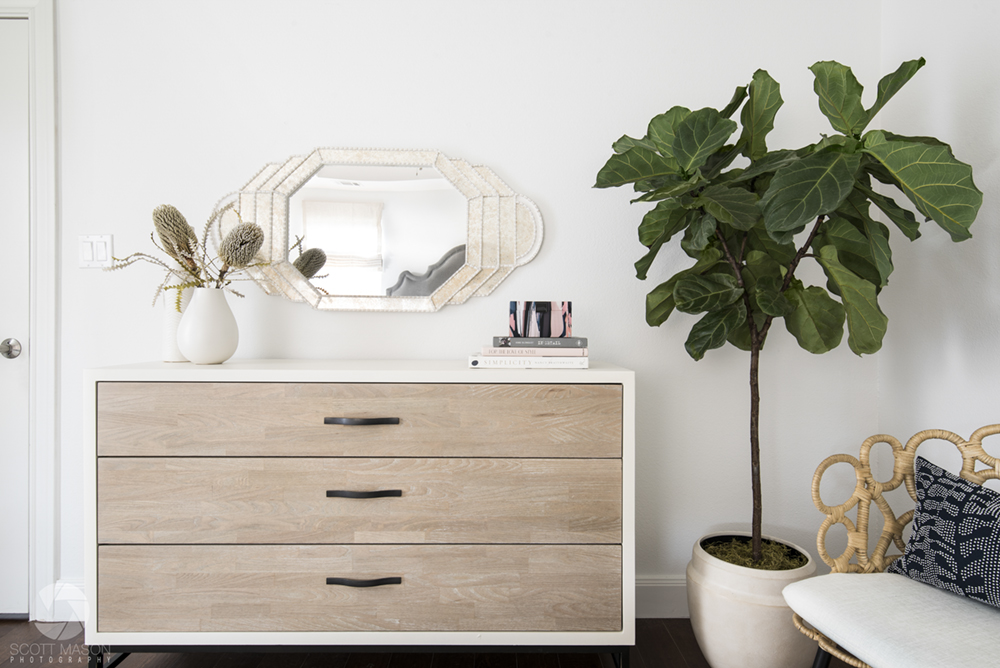 a one-point perspective interior design photo of a dresser, plant and chair against a white wall with a mirror on it