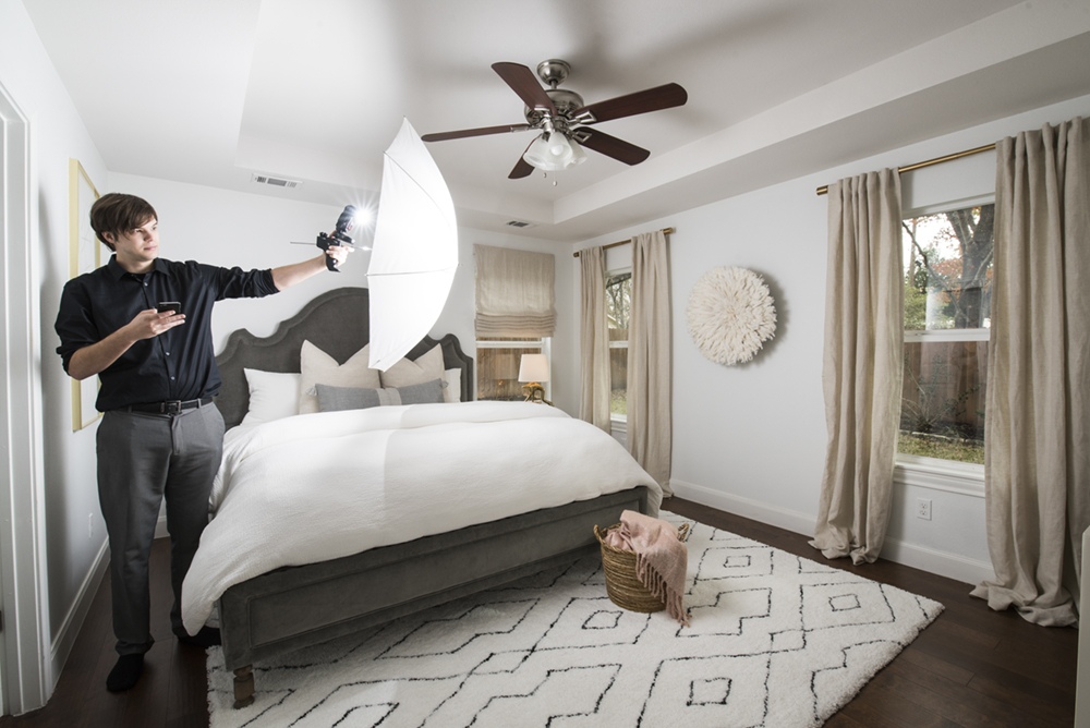 an image of a photographer hand-holding a flash umbrella in a bedroom