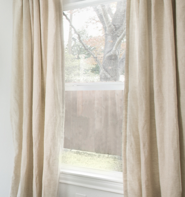 a crop of a window with beige curtains and a fence and tree outside