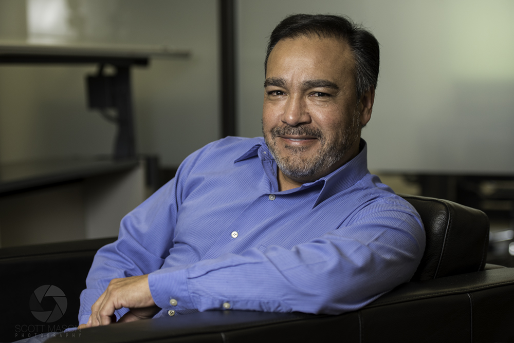a corporate portraits of a man leaning on a chair, smiling