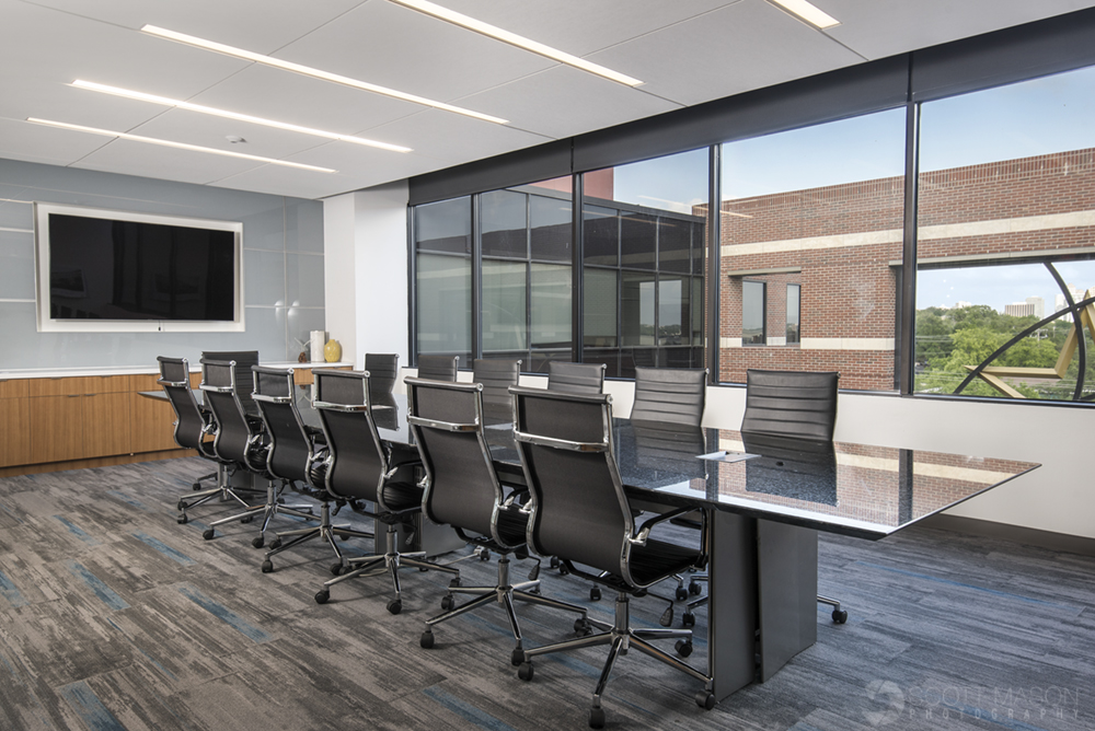 a photo of a conference room showing a long conference table, window and television screen