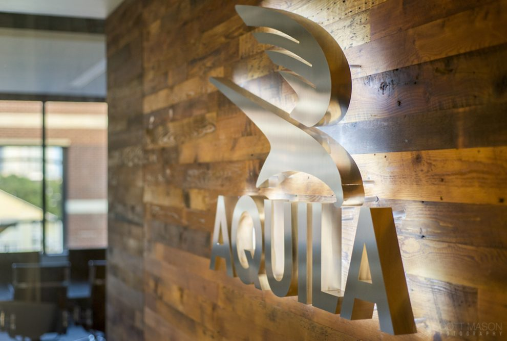 a close-up photo of the lit-up Aquila Commercial logo emblem in their lobby