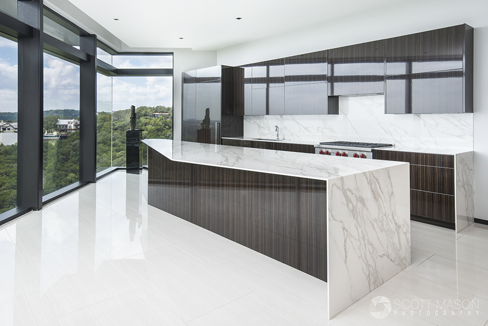 an interior architectural photo of a kitchen with a large stone cooking island
