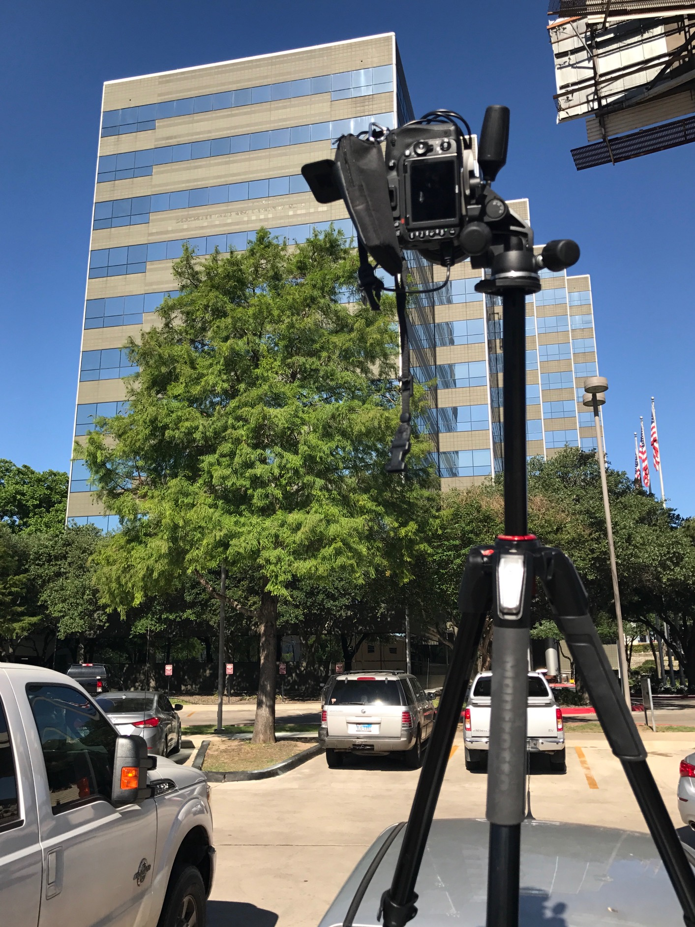 a snapshot of a camera on a tripod which is on top of a car, pointed at a building