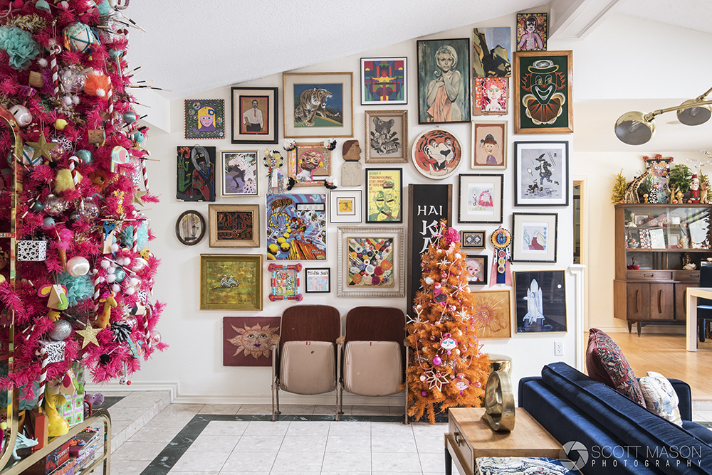 A gallery wall with several artworks and two christmas trees