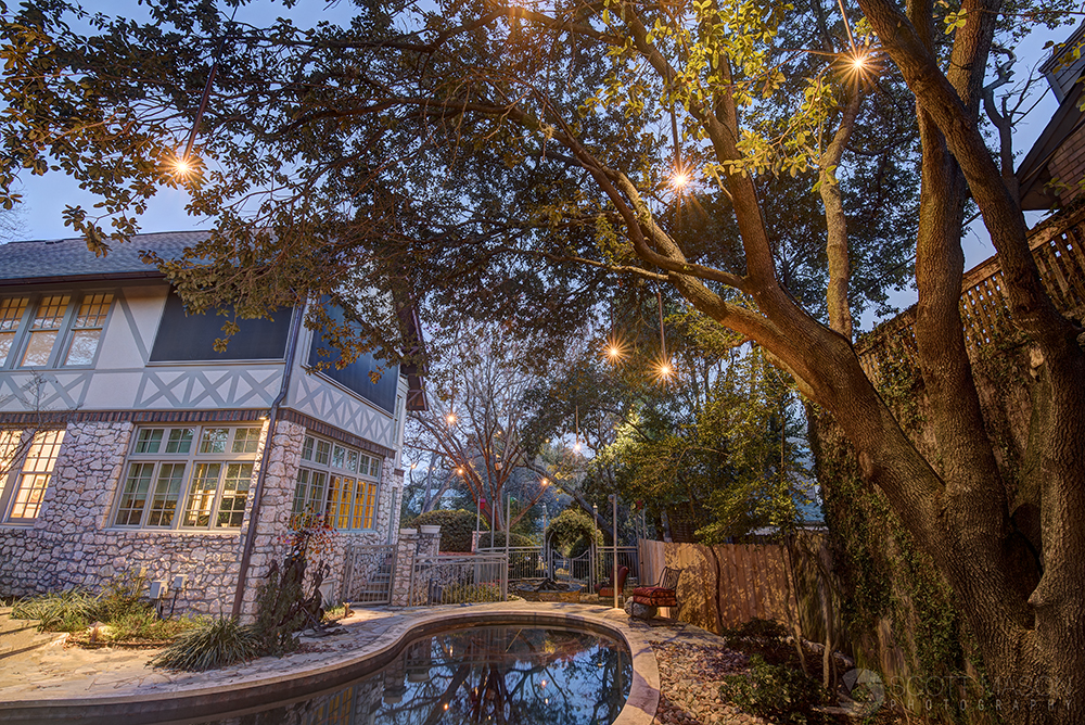 a photograph showing hanging lights in a backyard over a pool