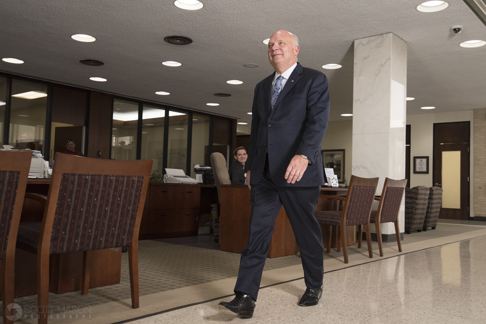 a corporate portrait of a CEO walking through his bank lobby