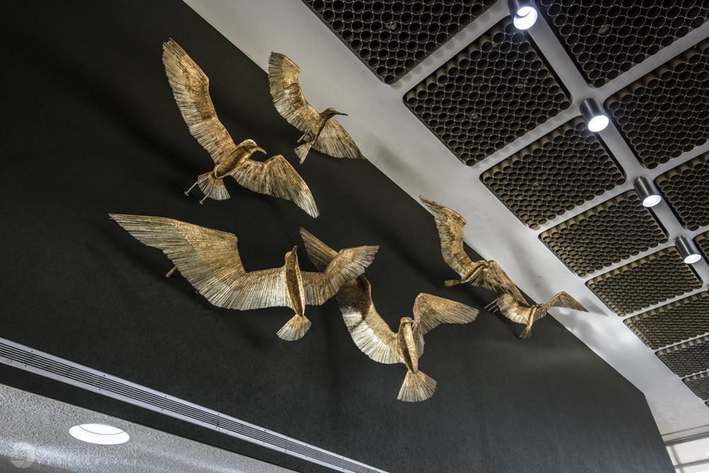 an architectural detail of golden birds on a high wall