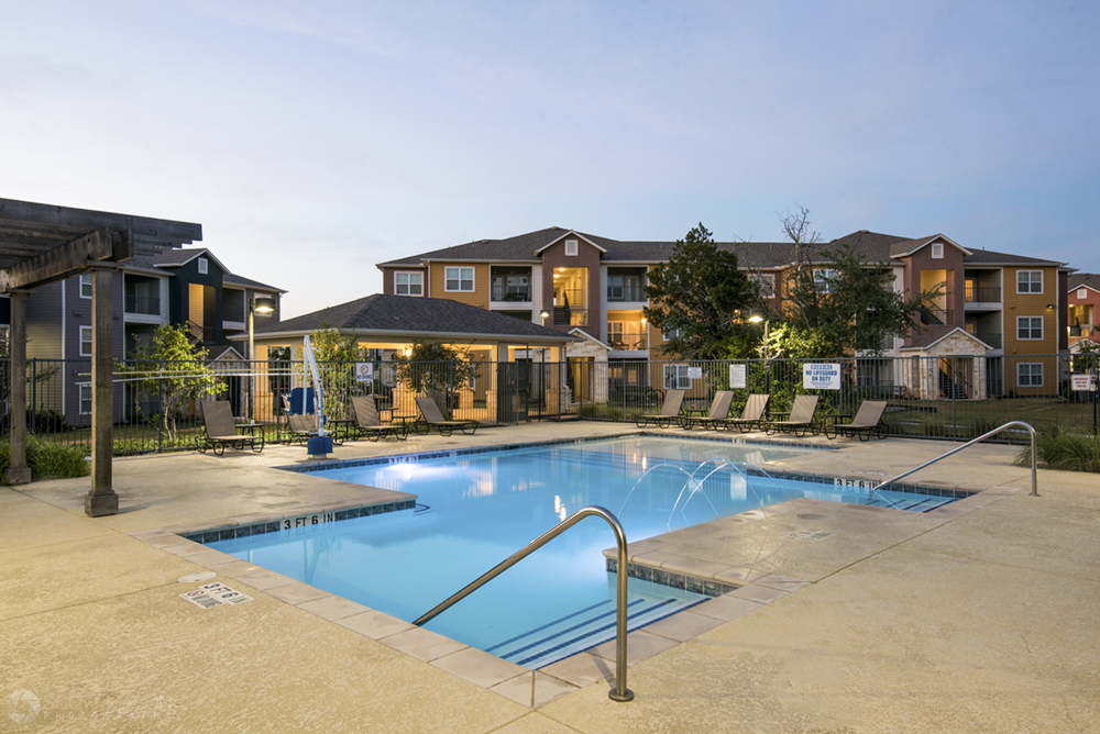 a twilight photo of a pool at William Cannon apartment homes in Austin