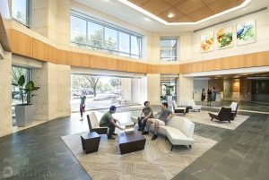 a wide view of an office lobby with people sitting around, and talking