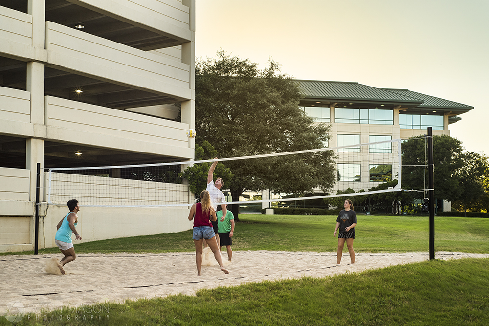 a lifestyle photo of people playing volleyball behind an office building at sunset