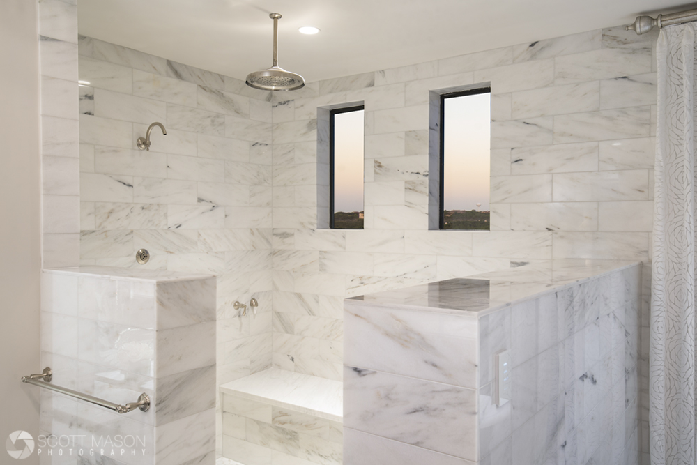 A high-end luxury shower made of white stone tile with windows