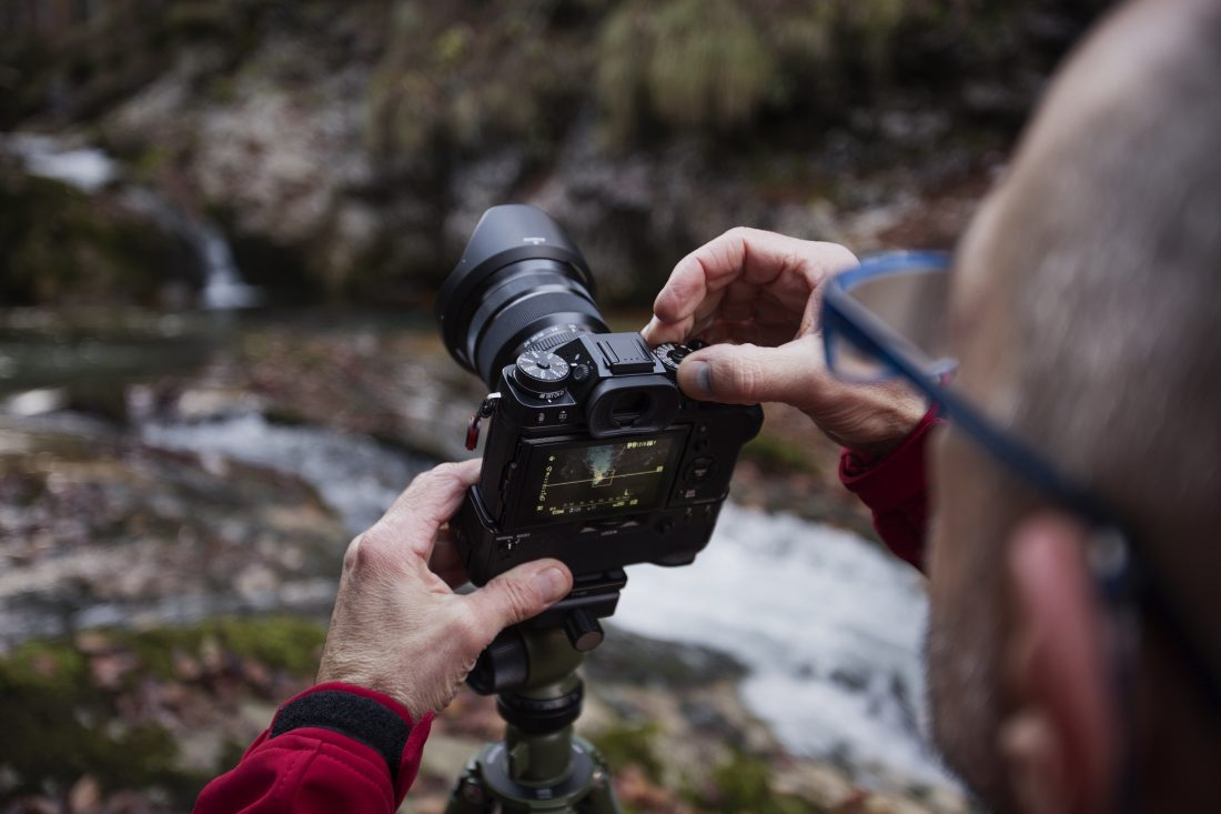 a man photographing a river with a mirrorless camera