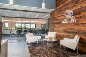 the lobby of Aquila Commercial's office with the conference room behind
