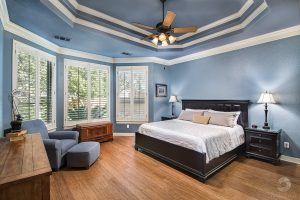 a photo of a master bedroom with wood floors and blue walls