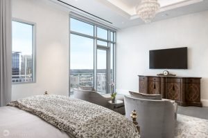an interior design photo of a luxury bedroom with a television and chandelier