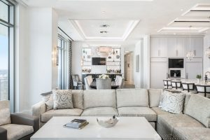 an interior photo of a luxury condo living room with a white couch and full bar