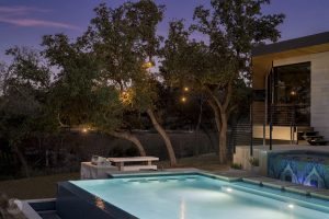 a phot of a pool in a back yard with exterior lighting on trees, at dusk