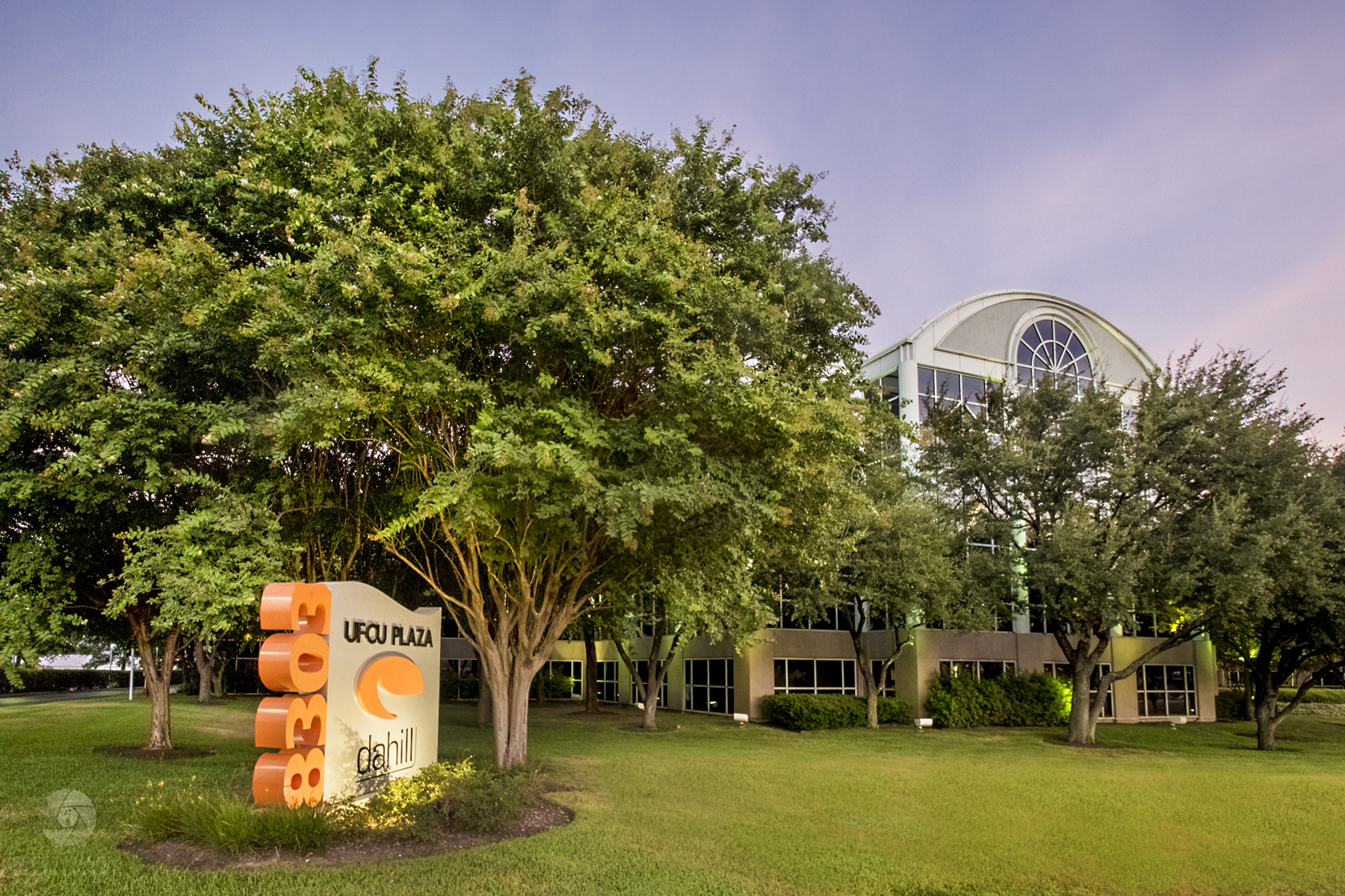 An exterior image of UFCU plaza in Austin with a monument sign and tree