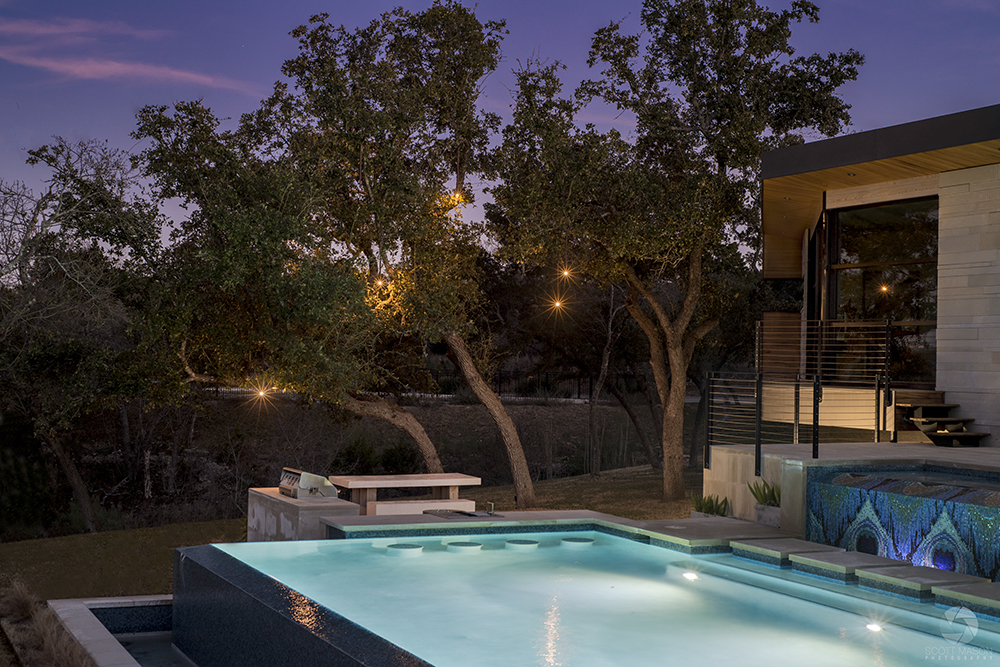 A twilight architectural photo of a pool and outdoor tree lighting in Austin, TX