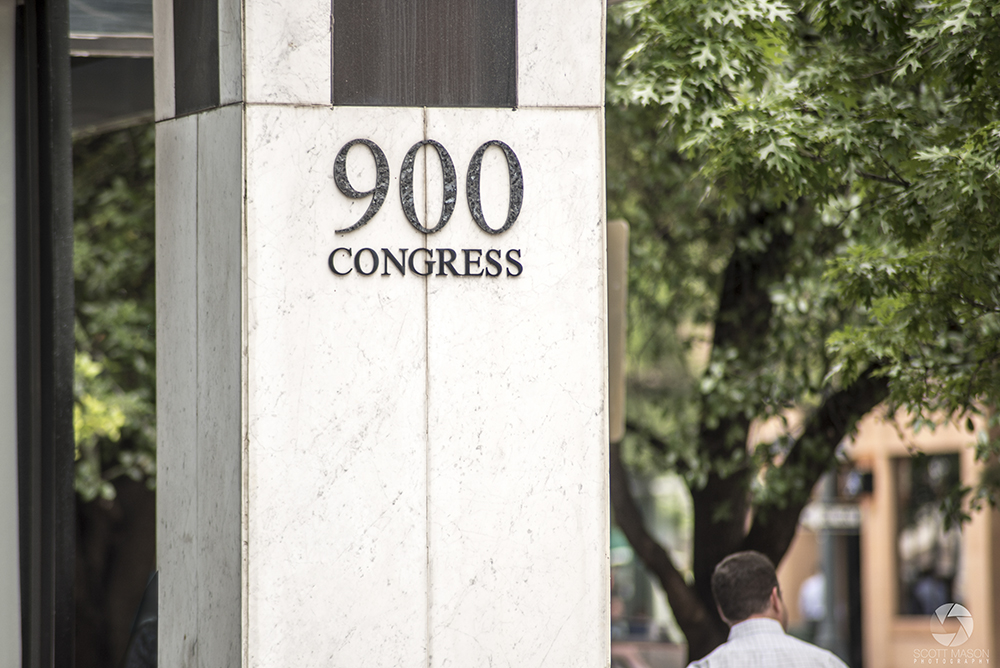 the address sign of 900 Congress with a man walking behind it