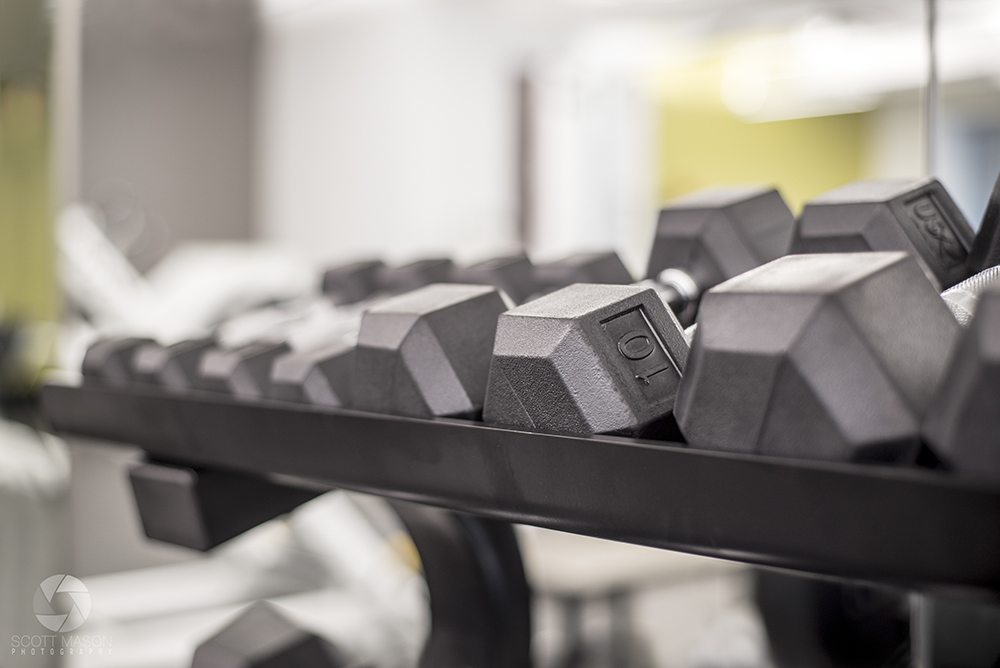 a close-up photo of dumbells on a weight rack