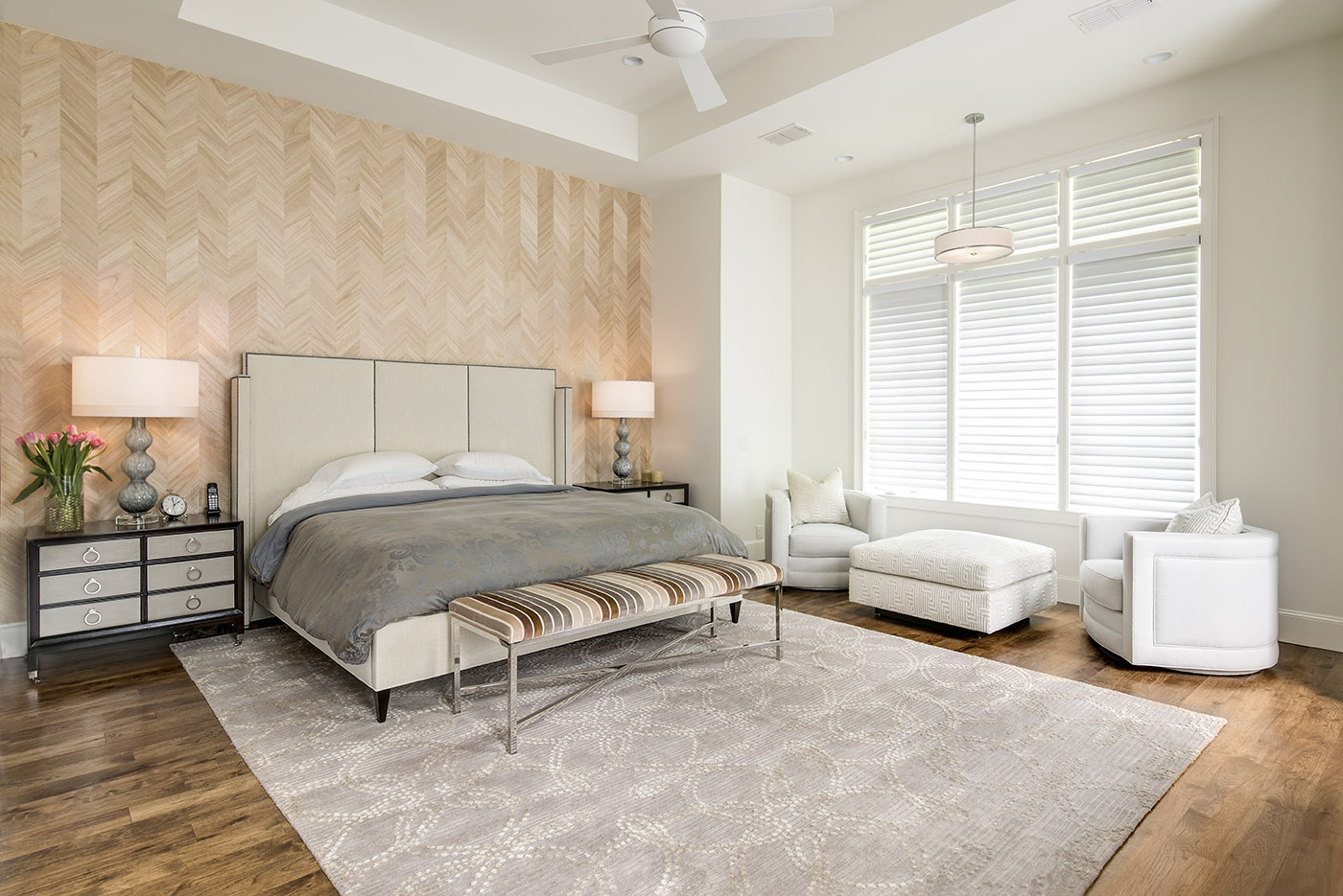 An interior design photo of a contemporary bedroom with wood floors and a grey carpet