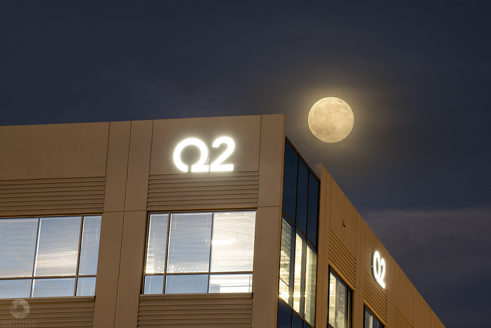 the corner of Q2's Austin building with the moon behind it