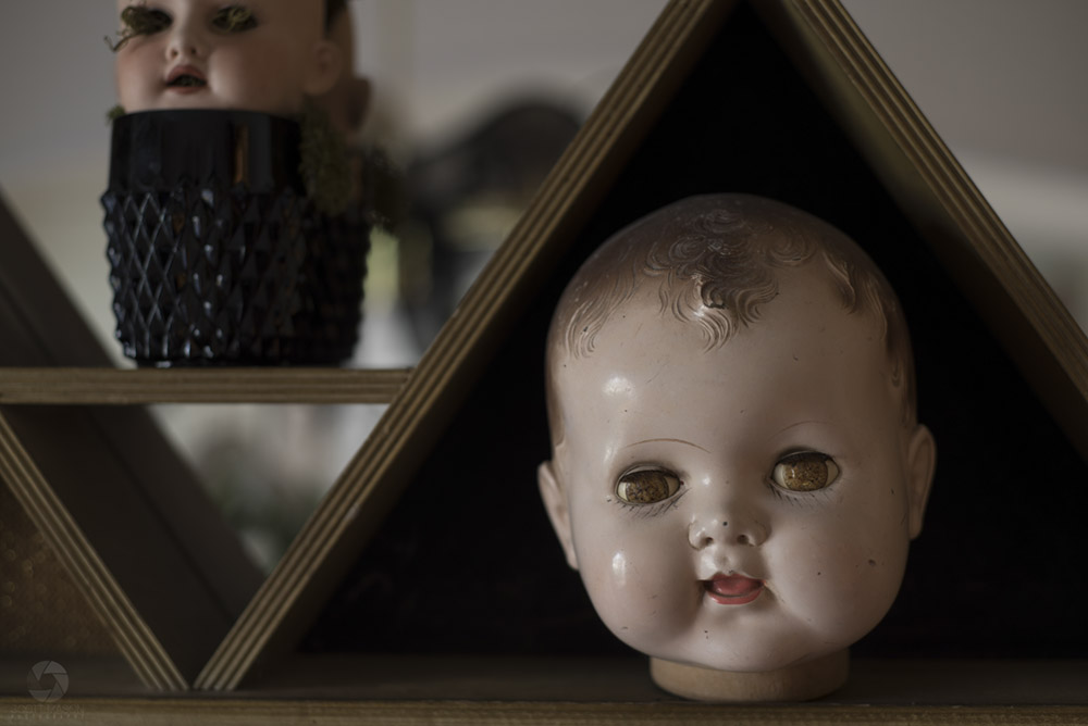 a creepy baby doll head on a shelf