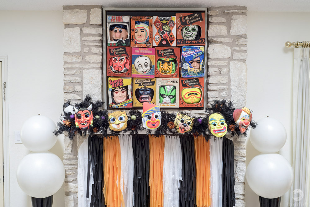 a detail shot of a fireplace mantel that is decorated with vintage masks