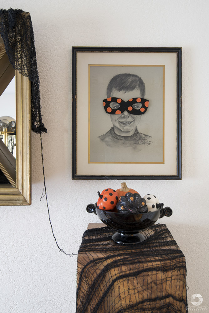 a one-point perspective photo of a wall with a child's portrait drawing and a decorative Halloween bowl