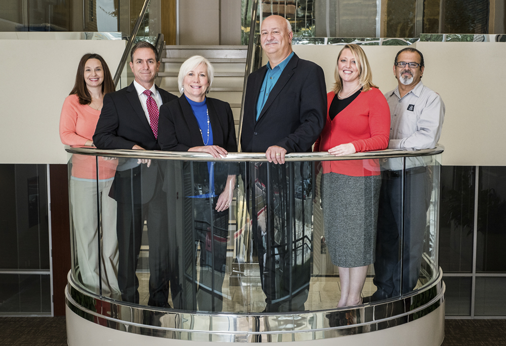 a photo of property managers from RMR Real Estate Services standing on a balcony at the Reserve At Bull Creek building