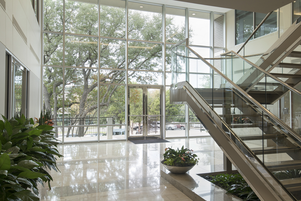a commercial real estate photo of the interior of a building entry with large glass windows