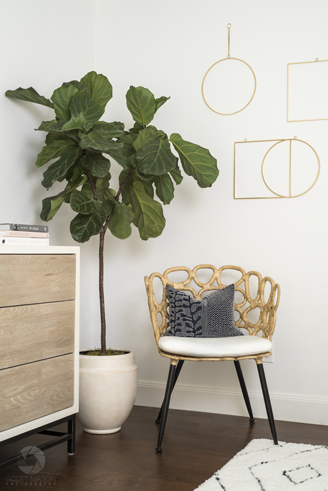 a vertical photo of an indoor potted plant next to a chair and part of a dresser