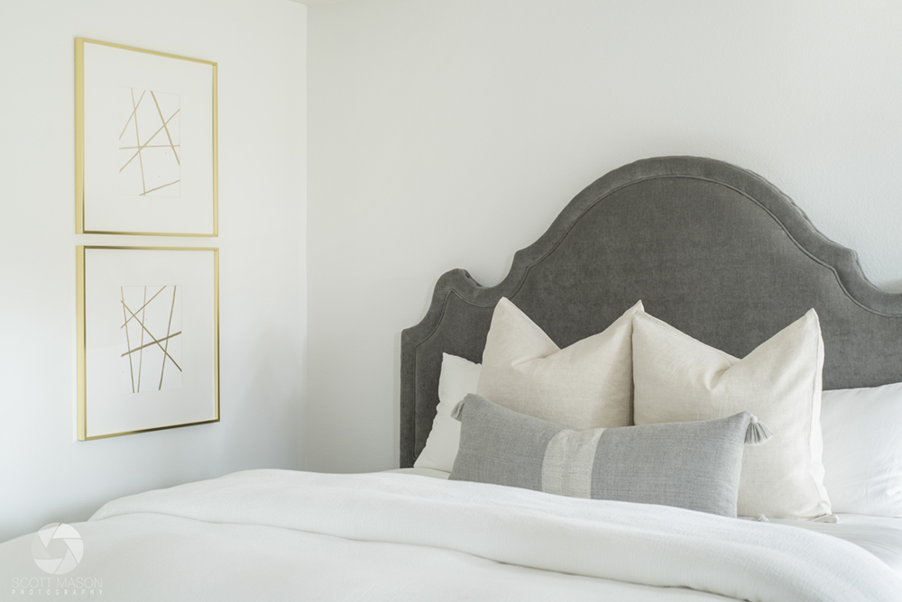 a cropped image of the corner of a room, with two picture frames over a bed