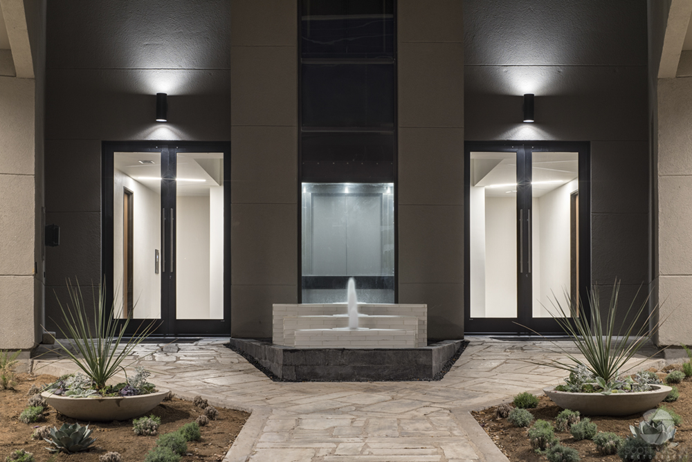 the rear entrance of an office building with a fountain