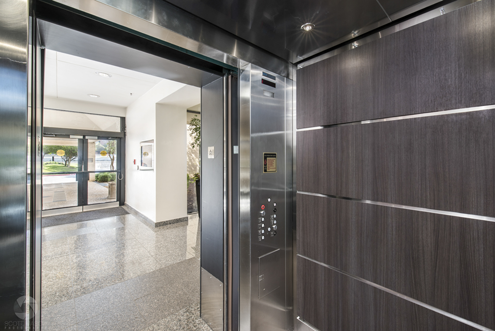 a photo from the inside of an elevator in an office building, with its doors open looking into the lobby