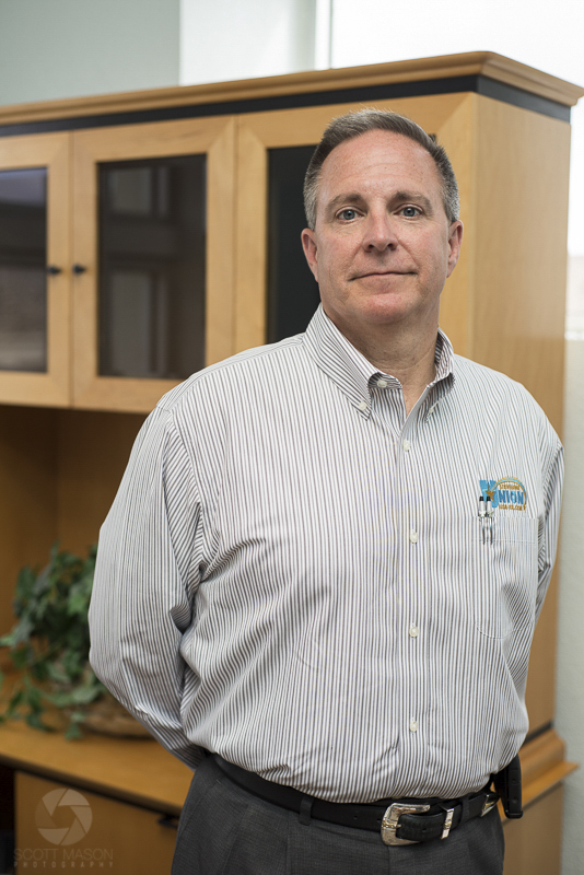 an executive portrait of a bank director standing in his office