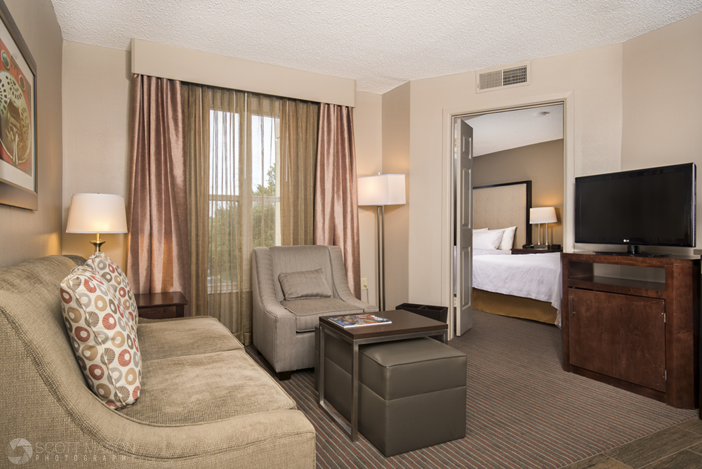 an interior photo of a standard double hotel suite with couch, television, chair and beds