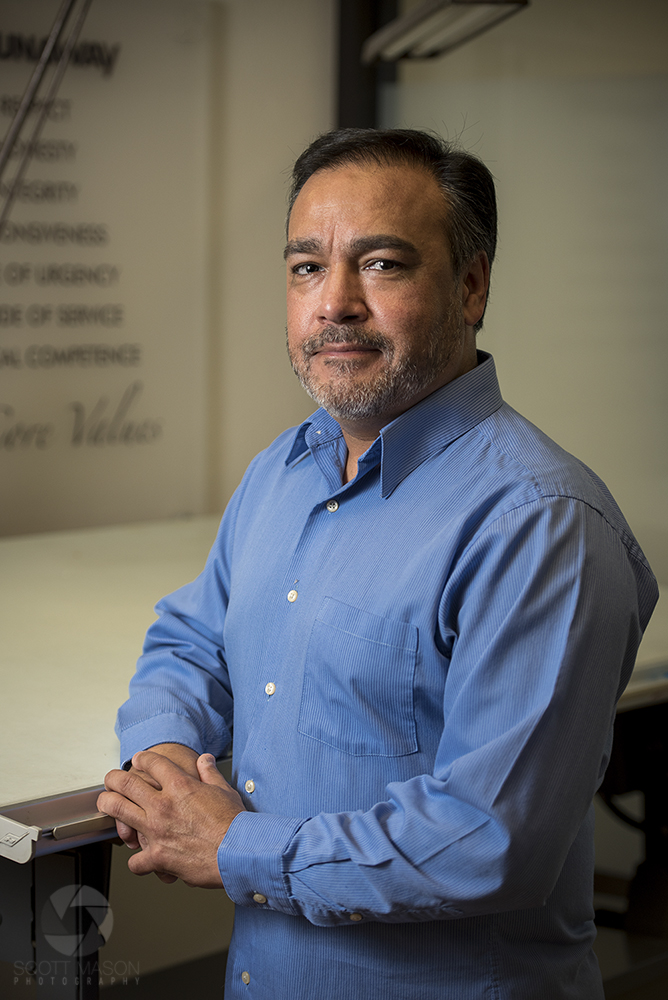 a man posing at a desk in an office