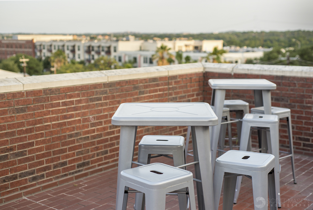 a close-up phot of chairs and tables on a brick patio at sunset