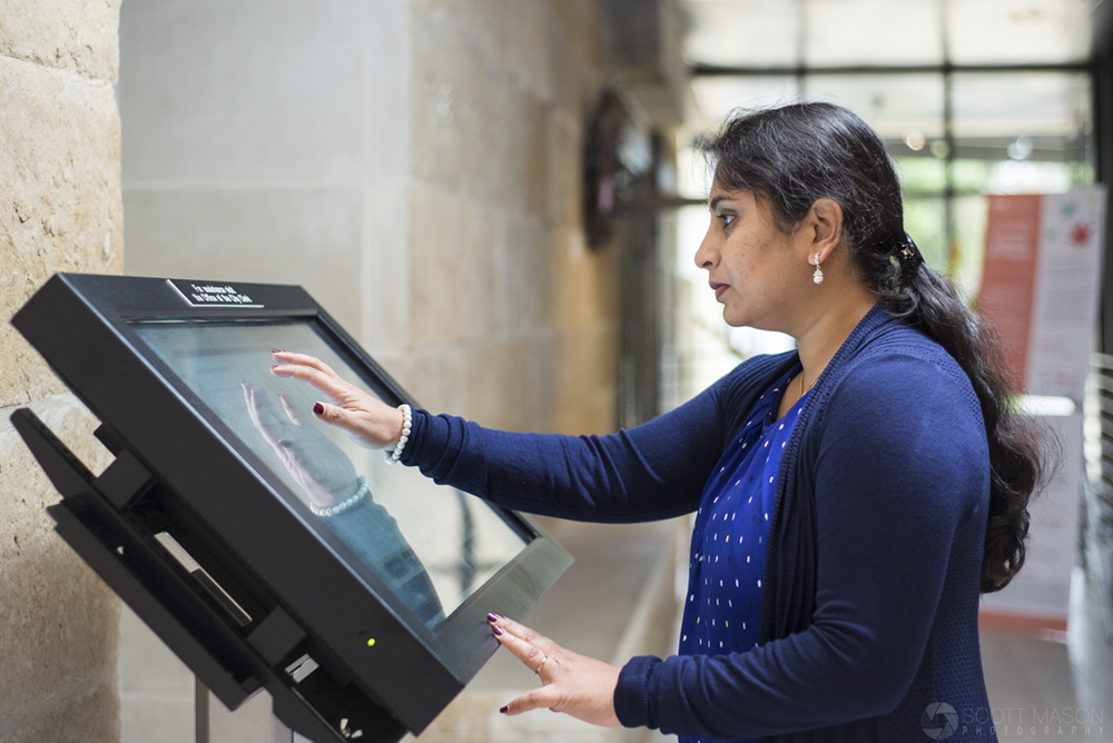 a woman at an electronic kiosk touching the display