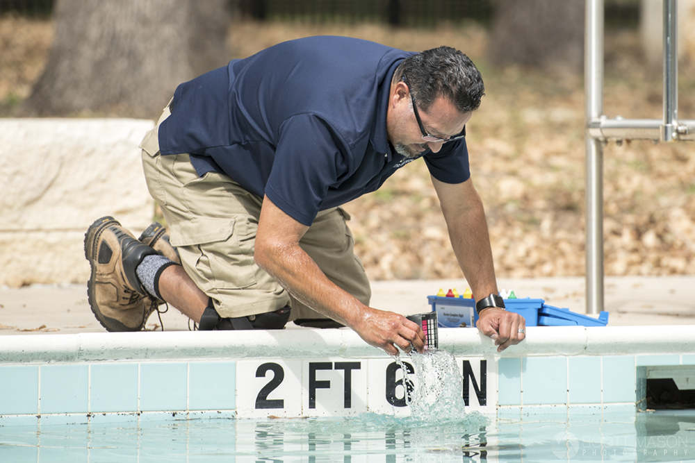 a city worker checking water levels in a pool
