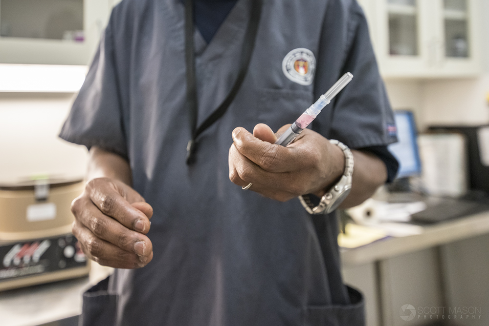 a city-owned rescue worker holding a syringe with a vaccine in it