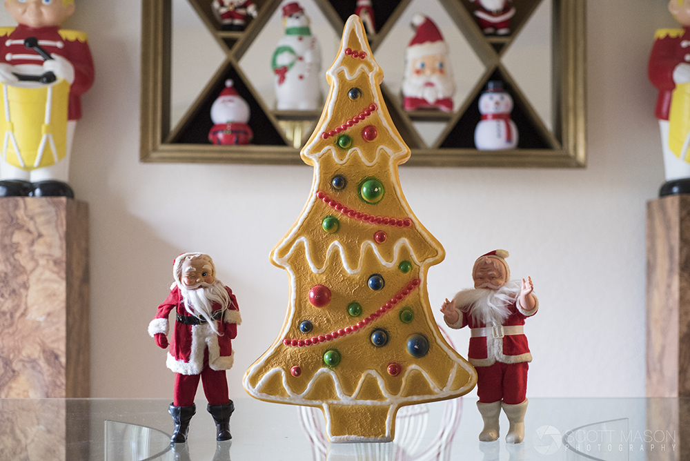 two miniature santas on a table with a gingerbread christmas tree ornament between them